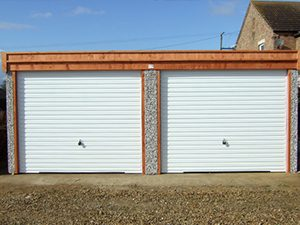 A double pent apex garage with 2 white doors